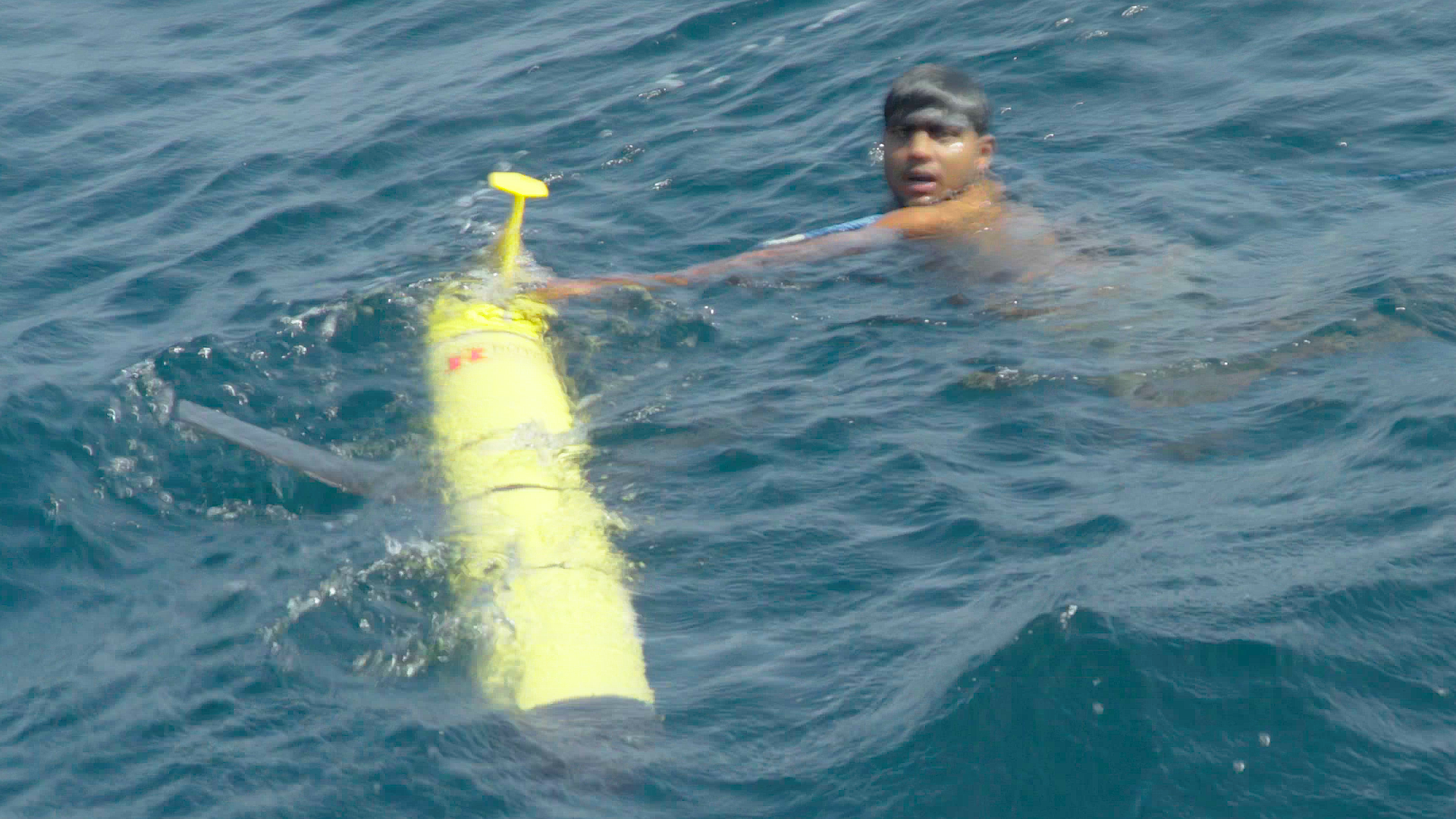A swimmer from the Sri Lankan recovery vessel is the first to touch RU29 on September 30, 2017 after 330 days at sea.