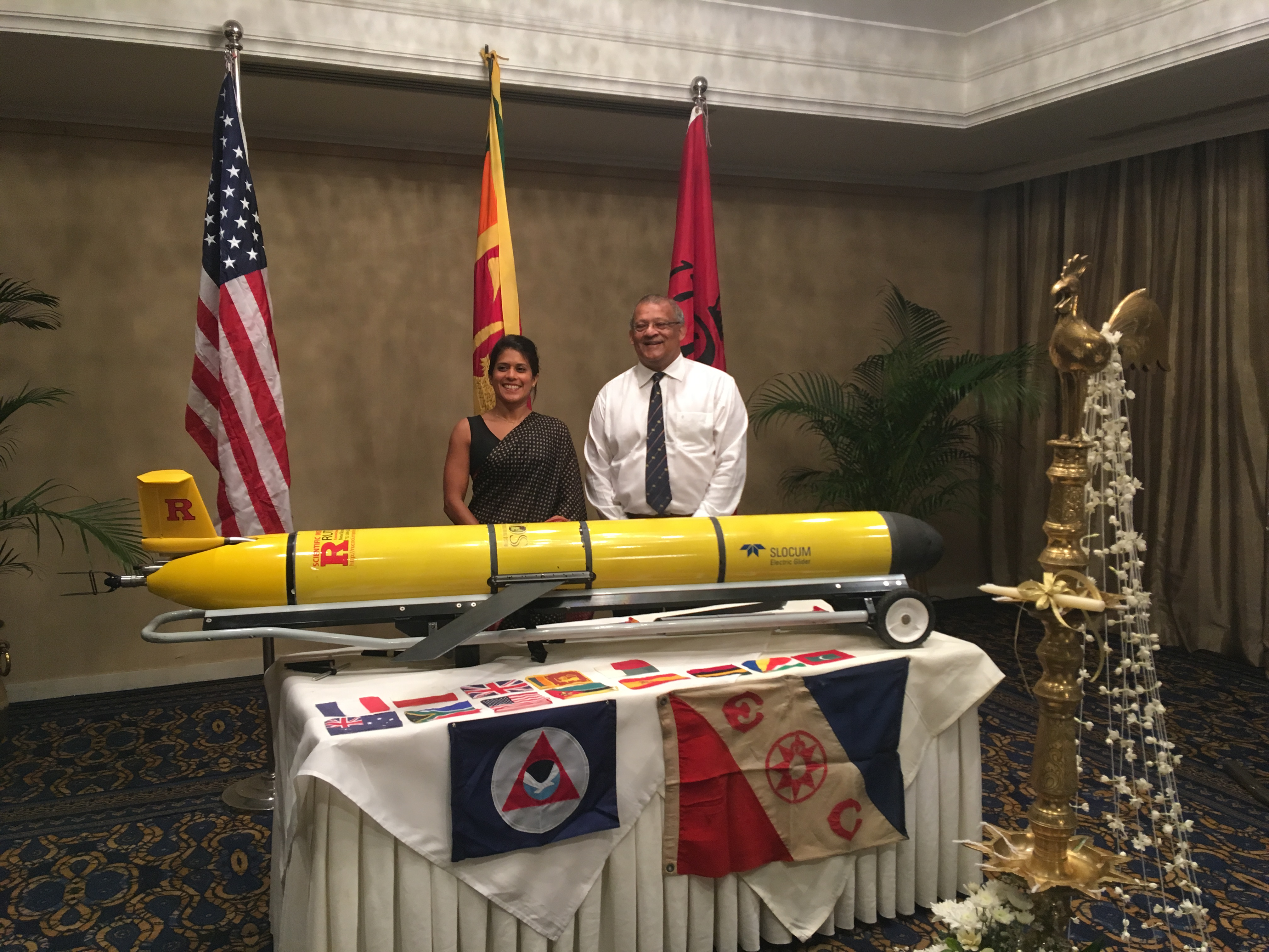 RU29 is prepared for a welcoming ceremony in Colombo, Sri Lanka organized by Prof. Chari Pattiaratchi (right). Dr. Asha de Vos (left) served as Master of Ceremonies. Displayed flags include U.S., Sri Lanka and Rutgers (on stands), NOAA and Explorers Club (side of table), and the international partners (tabletop). A traditional Sri Lanka oil lamp was lighted to open the ceremony.