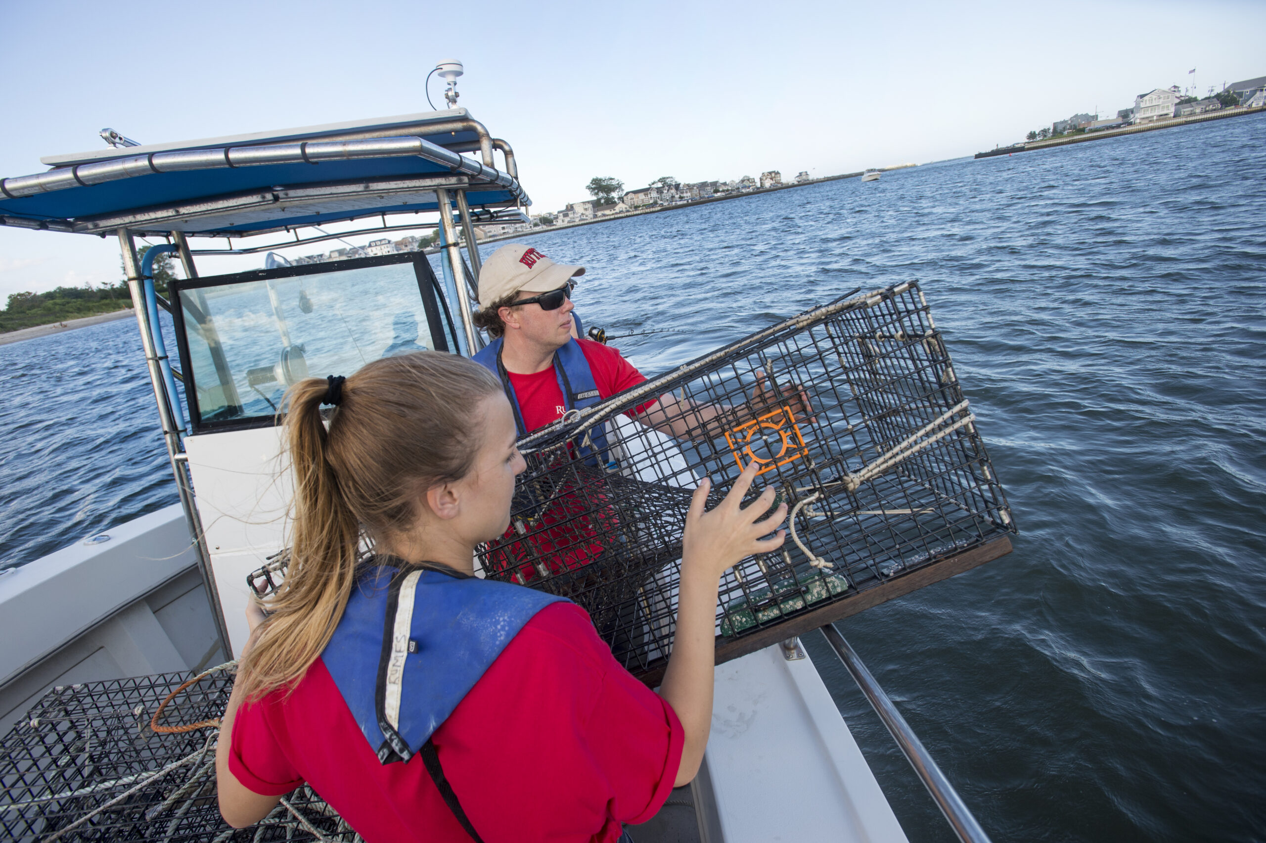 DMCS associate professor Olaf Jensen works with RIOS intern Maura Glovins (University of South Carolina'21 to lower lobster traps as part of a summer research team of faculty and undergraduate students that conduct fish and lobster monitoring
